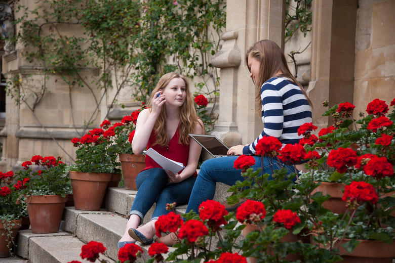 Girls sitting on steps surrounded by red flowers