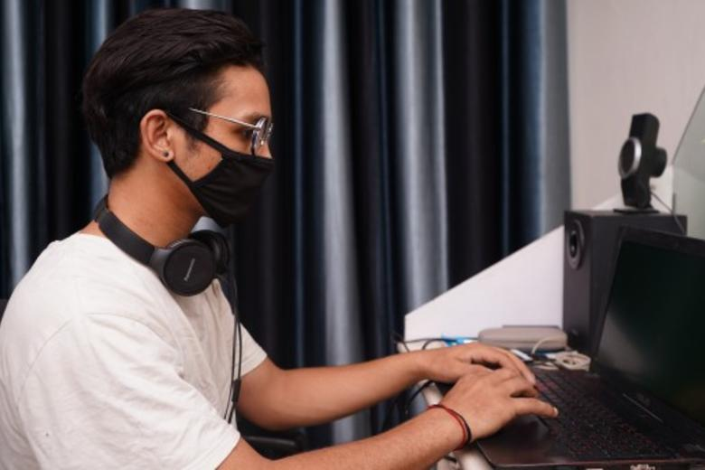 young man wearing face covering and typing on a laptop